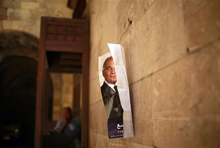 A man sits outside a shop as a poster of presidential candidate Ahmed Shafiq is seen hanging on a wall in Cairo June 13, 2012. REUTERS/Suhaib Salem