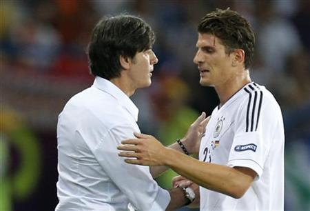 Germany's Mario Gomez (R) shakes hands with his coach Joachim Loew as he leaves the pitch during their Group B Euro 2012 soccer match against Netherlands at the Metalist stadium in Kharkiv, June 13, 2012. REUTERS/Thomas Bohlen