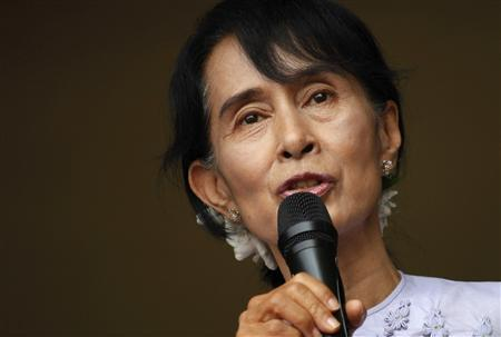 Myanmar's pro-democracy leader Aung San Suu Kyi addresses supporters and reporters from behind the gates of the National League for Democracy (NLD) office in Yangon, in this April 2, 2012 file photo. REUTERS/Damir Sagolj/FIles