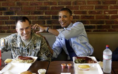 U.S. President Barack Obama jests with U.S. Army 1st Lt. Bill Edwards as they eat at Kenny's BBQ in honor of the upcoming Father's Day weekend in Washington June 13, 2012. REUTERS/Kevin Lamarque