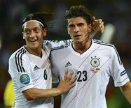 Немецкие футболисты Марио Гомес (справа) и Месут Озил радуются голу, забитому в ворота команды Нидерландов, 13 июня 2012 года. Сборная Германии сделала большой шаг к плей-офф Евро-2012, обыграв в среду вечером со счетом 2-1 команду Нидерландов, рискующих так и не выйти из группы. REUTERS/Felix Ordonez