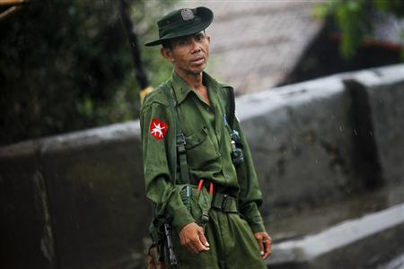 A soldier stands in the rain as he secures a major street in Sittwe June 13, 2012. Soldiers and riot police patrolled the streets of the Myanmar town of Sittwe on Wednesday to enforce a state of emergency after days of sectarian violence in which at least 21 people have been killed. REUTERS/Soe Zeya Tun