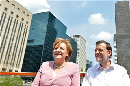 Germany's Chancellor Angela Merkel (L) smiles next to Spain's Prime Minister Mariano Rajoy on board a boat before the start of the NATO summit in Chicago May 20, 2012. Picture taken May 20, 2012. REUTERS/La Moncloa/Handout/Files