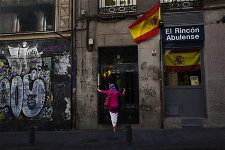 A woman stands next to Spanish flags as she waits to enter a building in central Madrid June 13, 2012. REUTERS/Susana Vera