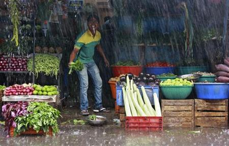 A vendor smiles while standing at his roadside vegetable stall during monsoon rains in Kochi June 12, 2012. REUTERS/Sivaram V