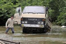 Водитель около грузовика на залитой наводнением улице в пригороде Владивостока 22 июля 2009 года. Дождь смыл участок только что построенной автотрассы, по которой главы крупнейших стран будут съезжаться на саммит АТЭС в сентябре, когда Владивосток ждет очередной сезон тайфунов. REUTERS/Yuri Maltsev