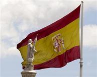 Статуя Христофора Колумба на фоне испанского флага в Мадриде, 11 июня 2012 года. Испания хочет к понедельнику завершить проверку своих банков, которая покажет, сколько им нужно денег для рекапитализации, сообщили Рейтер два источника, причем один добавил, что сумма может составить 60-70 миллиардов евро ($75-$88 миллиардов). REUTERS/Paul Hanna