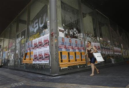 A woman walks past a closed shop with election campaign posters of Democratic Left party and radical left SYRIZA party on it in central Athens June 14, 2012. REUTERS/John Kolesidis (GREECE)