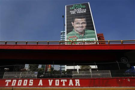 A picture of Enrique Pena Nieto, candidate of the opposition Institutional Revolutionary Party (PRI), is seen on a billboard, above a graffiti which reads: ''Everyone to vote'', in a neighborhood in Mexico city June 13, 2012. REUTERS/Edgard Garrido