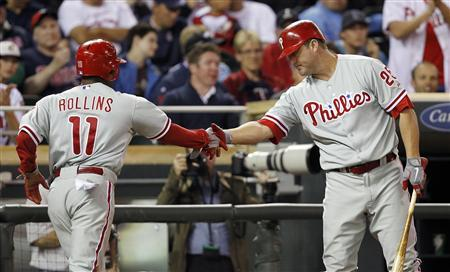 Philadelphia Phillies Jimmy Rollins (11) is congratulated by teammate Jim Thome (R) after he scores on a hit by Phillies Placido Polanco against Minnesota Twins pitcher Jeff Gray during the ninth inning of their interleague MLB baseball game at Target Field in Minneapolis June 14, 2012. REUTERS/Eric Miller