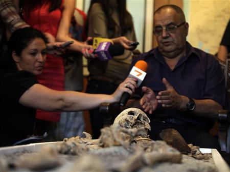 National History Museum head Bozhidar Dimitrov (R) speaks to the media near a skeleton pierced with a piece of iron during a media event at the National History Museum in Sofia June 14, 2012. REUTERS/Stoyan Nenov