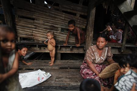 Myanmar Rohingya people pass their time at their slum near the sea, in the town of Sittwe in this May 19, 2012 file photo. REUTERS/Damir Sagolj/Files
