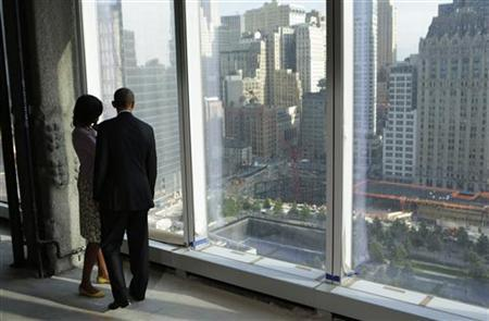 U.S. President Barack Obama and first lady Michelle Obama look down at the 9/11 Memorial while touring the One World Trade Center building which is under construction in New York June 14, 2012. REUTERS/Kevin Lamarque