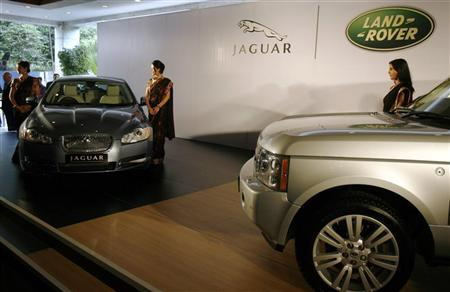 Models pose with a Jaguar XF and Range Rover during the launch of Jaguar and Land Rover in India, after a news conference in Mumbai June 28, 2009. REUTERS/Punit Paranjpe/Files