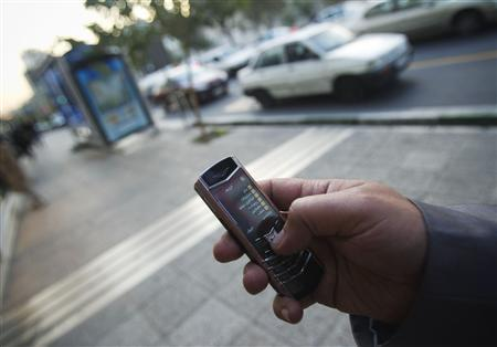 An Iranian man uses a mobile phone while standing on a street in northern Tehran in this October 24, 2010 file photo. REUTERS/Morteza Nikoubazl/Files