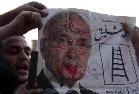 Protesters hold up a defaced poster of presidential candidate Ahmed Shafik, ousted leader Hosni Mubarak's last prime minister, at Tahrir square in Cairo June 14, 2012. REUTERS/Mohamed Abd El Ghany