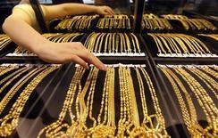 Работница ювелирного магазина в китайском городе Вухань раскладывает на витрине золотые украшения, 25 августа 2011 года. Цены на золото держатся выше $1.620 в ожидании итога выборов в Греции, которые пройдут в воскресенье. REUTERS/Stringer