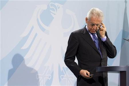 Italian Prime Minister Mario Monti checks his phone during a joint news conference with German Chancellor Angela Merkel after talks at the Chancellery in Berlin, January 11, 2012. REUTERS/Thomas Peter