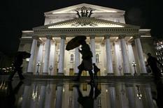 Люди проходят мимо Большого театра дождливым московским вечером 12 октября 2011 года. Плохая погода, установившаяся в Москве на рабочей неделе, останется в столице и на выходные, но будет тепло, ожидают синоптики. REUTERS/Anton Golubev