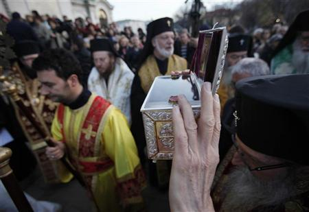 A Bulgarian East-Orthodox priest holds up a box containing bones, believed to be the relics of John the Baptist, in front golden-domed ''Alexander Nevski'' cathedral in Sofia, November 12, 2010. The bones, discovered earlier this year in excavation works in the town of Sozopol on the Black Sea coast, will be displayed in ''Alexander Nevski'' cathedral for several days. REUTERS/Oleg Popov