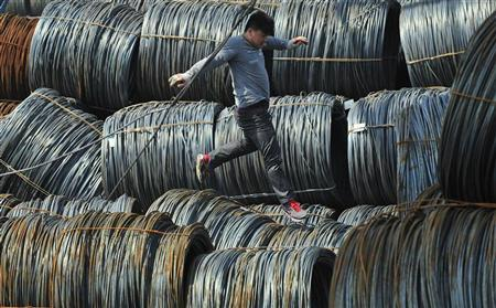 A labourer walks on coils of steel wire at a steel market in Shenyang, Liaoning province April 13, 2012. REUTERS/Sheng Li