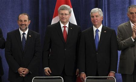 Canadian Minister of Transport, Infrastructure and Communities Denis Lebel (L) , Canadian Prime Minister Stephen Harper (C) and Michigan Governor Rick Snyder stand together after signing an agreement to build a new public bridge between Detroit, Michigan and Windsor, Canada following a press conference in Detroit, Michigan June 15, 2012. REUTERS/Rebecca Cook