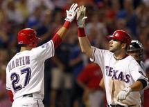 Texas Rangers' Mitch Moreland is congratulated by Leonys Martin (L) after hitting a home run against the Houston Astros in the eighth inning of their MLB interleague baseball game in Arlington, Texas June 15, 2012. REUTERS/Mike Stone