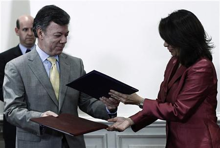 Costa Rica's President Laura Chinchilla and Colombia's President Juan Manuel Santos exchange documents after signing bilateral agreements during a meeting in San Jose June 15, 2012. REUTERS/Juan Carlos Ulate