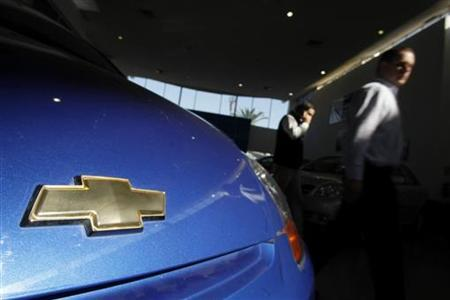 Pedestrians walk past a Chevrolet vehicle in a showroom at Santiago June 1, 2009. REUTERS/Ivan Alvarado