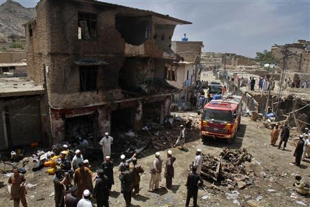 Security officials, residents and members of the media gather at the site of a bomb attack in Landi Kotal, northwest Pakistan June 16, 2012. The bomb planted in a pickup truck killed at least 13 people at the market in northwest Pakistan on Saturday and the death toll could rise, security and hospital officials said. REUTERS/Shahid Shinwari