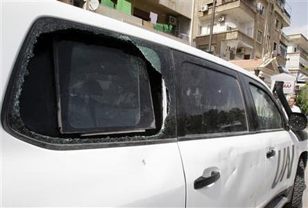 A damaged United Nations (U.N.) vehicle used by members of the U.N. observers mission in Syria, is seen near a hotel in Damascus June 16, 2012. United Nations observers monitoring the turmoil in Syria suspended operations on Saturday in response to escalating violence which threatens to kill off a tattered peace plan brokered by international mediator Kofi Annan. REUTERS/Khaled al- Hariri