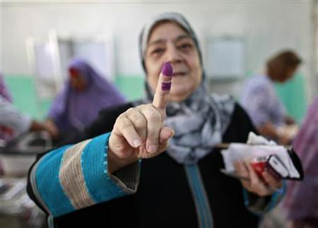 A woman shows her ink-stained finger after casting her vote at a polling station in Cairo June 16, 2012. REUTERS/Suhaib Salem