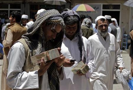 Money changers count piles of Afghani at a money exchange market in Kabul June 16, 2012. REUTERS/Mohammad Ismail
