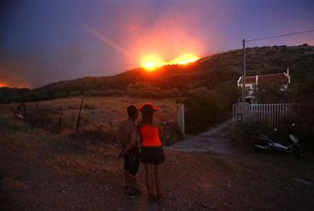 Locals look at a forest fire approaching their house at Thymari coastal village, 40 km (25 miles) southeast of Athens, June 16, 2012. REUTERS/Yannis Behrakis