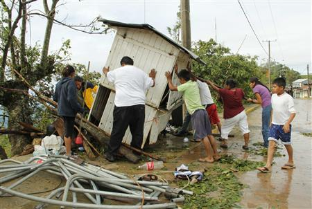 Residents push a stall knocked down by Hurricane Carlotta in the community of Pluma Hidalgo, in the Mexican state of Oaxaca June 16, 2012. Carlotta weakened into a tropical depression on Saturday after battering Mexico's Pacific coast and killing at least two children whose house collapsed in a landslide. REUTERS/Jorge Luis Plata