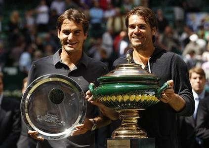 Tommy Haas (R) of Germany and Roger Federer of Switzerland present their trophies during the victory ceremony at the men's singles final of the Halle Open ATP tennis tournament in Halle June 17, 2012. REUTERS/Ina Fassbender