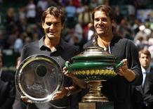 Tommy Haas (D) da Alemanha e Roger Federer da Suíça apresentam seus troféus na final do Aberto de Halle neste domingo. 17/06/2012 REUTERS/Ina Fassbender