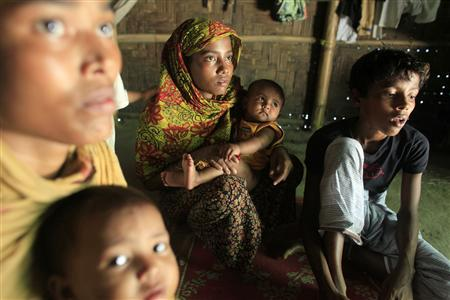 Rohingya women and children hide in a house in Teknaf June 17, 2012. The group of 7 Rohingya Muslims fled mass burning of houses and violence in Myanmar, setting out in a wooden boat for neighbouring Bangladesh. They were pushed back three times by border guards, but finally made it on their fourth attempt and are now hiding with local villagers to avoid being arrested. REUTERS/Andrew Biraj