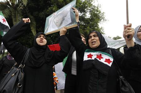 Syrians living in Algeria wave a poster of a girl, whom they say is a victim of President Bashar al-Assad's forces, during a protest outside the Syrian embassy in Algiers June 16, 2012. Escalating violence in Syria forced United Nations observers to suspend operations on Saturday. Chief monitor General Robert Mood blamed both government troops and rebels for the relentless conflict, in which Assad's forces are trying to crush an increasingly well-armed insurgency which grew out of a 15-month-old wave of protests. REUTERS/Louafi Larbi