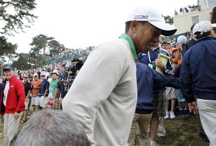 Tiger Woods reacts after colliding with a photographer while walking off the 18th green at the conclusion of his third round of the 2012 U.S. Open golf tournament on the Lake Course at the Olympic Club in San Francisco, California June 16, 2012. REUTERS/Danny Moloshok
