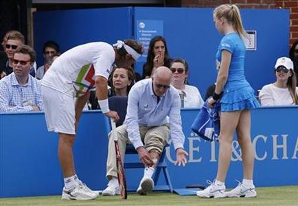 David Nalbandian of Argentina (L) looks on as line judge Andrew McDougall shows his injury after he kicked a hoarding during his men's singles final match against Marin Cilic of Croatia at the Queen's Club tennis tournament in London June 17, 2012. Nalbandian lost the match by default. REUTERS/Suzanne Plunkett