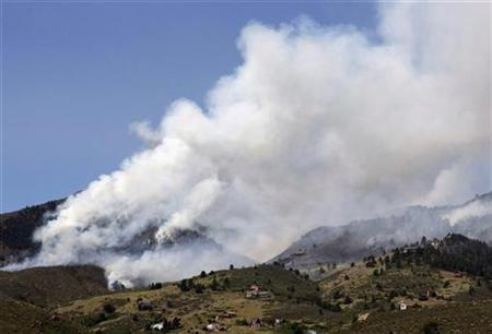 A huge plume of smoke rises from Colorado's High Park Fire, with dozens of homes visible in the foreground about 15 miles northwest of Fort Collins June 11, 2012. REUTERS/Rick Wilking