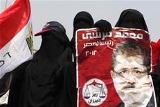 """Сторонники египетских """"Братьев-мусульман"""" держат плакат с изображением Мохаммеда Мурси в Каире, 18 июня 2012 года. Египетские исламисты """"Братья-мусульмане"""" заявили в понедельник о победе своего кандидата на выборах президента страны. REUTERS/Asmaa Waguih"""