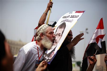 A supporter of the Muslim Brotherhood's presidential candidate Mohamed Morsy kisses a picture of him during a celebration at Tahrir square in Cairo June 18, 2012. The Muslim Brotherhood's Mohamed Morsy said on Monday after his group declared him winner in a presidential race that he would be a president for all Egyptians and said he would not 'seek revenge or settle scores.' REUTERS-Suhaib Salem