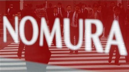 Pedestrians are reflected in a sign displayed outside a Nomura Securities branch in Tokyo February 2, 2011. . REUTERS/Kim Kyung-Hoon