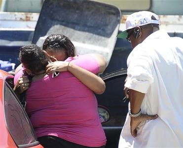 Rodney King's daughters Dene (L), and Candice King embrace as former bodyguard Johnnie Kelly stands by in front of their father's home where he was found dead in Rialto, a suburb east of Los Angeles June 17, 2012. King, who came to symbolize racial tensions in the United States after his 1991 beating at the hands of police which led to deadly riots in Los Angeles a year later, was found dead in a swimming pool. REUTERS/Gene Blevins