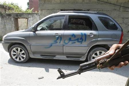 A Syrian soldier stands next to a car with ''Free Army'' written on it in Haffeh town near Latakia city June 14, 2012. REUTERS/Khaled al-Hariri