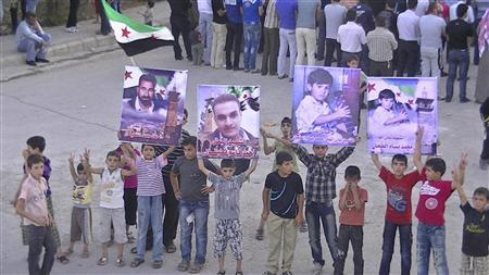 Boys hold posters of people whom protesters say were killed by forces loyal to Syria's President Bashar al-Assad, during a demonstration in Deraa June 17, 2012. Picture taken June 17, 2012. REUTERS/Shaam News Network/Handout