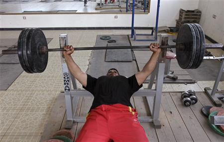 Disabled powerlifter Mohammad Fahim Rahimi trains with barbells in Kabul June 17, 2012. LREUTERS/Mohammad Ismail
