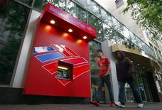 Pedestrians walk past a Bank of America ATM in Charlotte, North Carolina April 18, 2012. REUTERS/Chris Keane